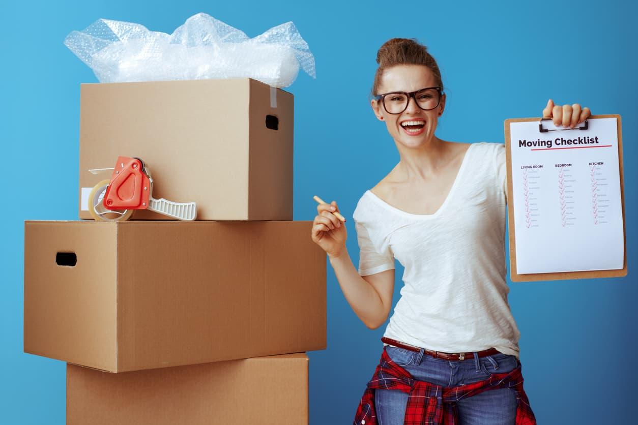 happy woman near cardboard box showing moving checklist on blue