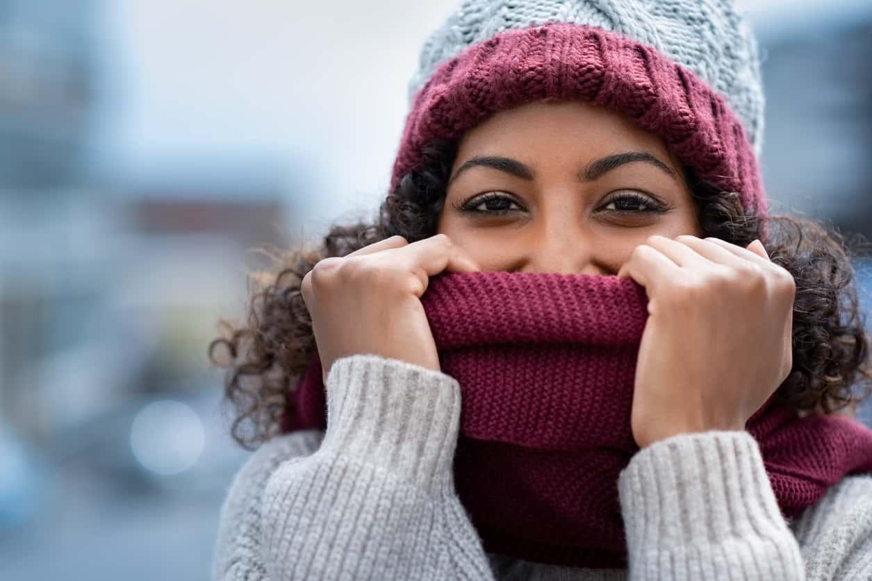 Beautiful woman hiding face in woolen scarf